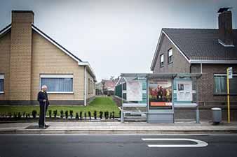 Blinde Herman Caulier wacht op de voeltegel naast de bushalte op de bus van De Lijn